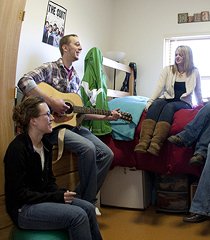 Students gather around a guitar player